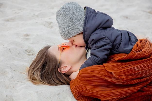 Erwachsene frau mit einem kleinkindjungen, der sich auf sand hinlegt.