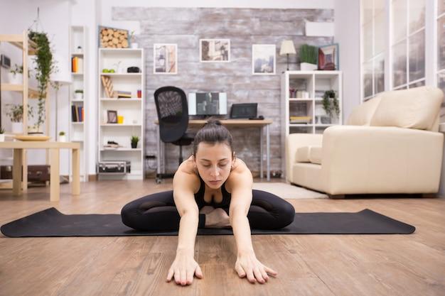 Erwachsene frau mit geschlossenen augen sitzt in lotus-yoga-pose, entspannt ihren rücken und streckt sich nach vorne.