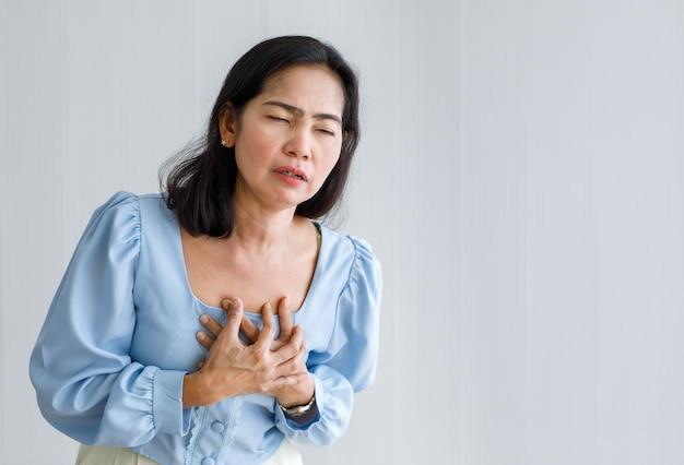 Erwachsene frau mit plötzlichem herzinfarkt und brust mit schmerzgesicht halten. konzept der notfallversorgung und betroffen von stauungsversagen oder herz-lungen-wiederbelebung, herzproblemen.