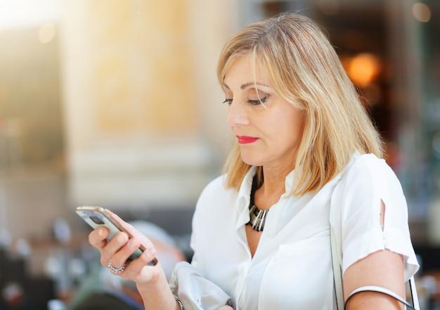 Erwachsene frau nutzt das smartphone