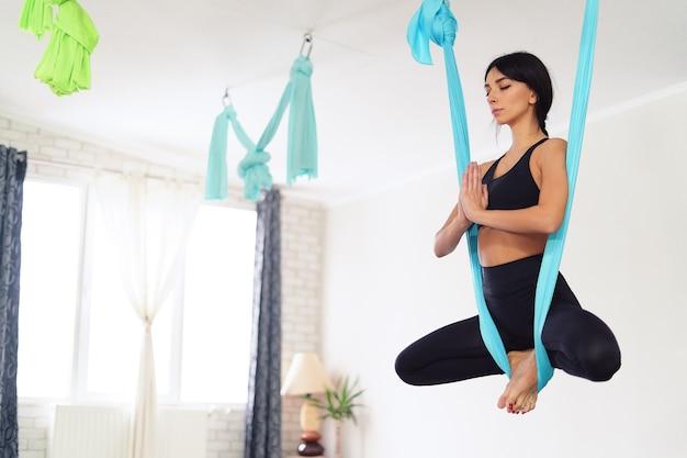 Erwachsene frau praktiziert anti-schwerkraft-yoga
