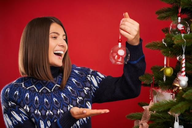 Erwachsene frau schmückt weihnachtsbaum auf rotem hintergrund