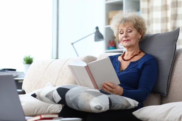 Erwachsene frau sitzen auf sofa zu hause und lesen buch.