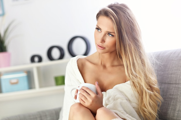 Erwachsene frau sitzt auf dem sofa mit kaffee
