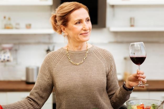 Erwachsene frau. strahlende gut aussehende reife frau in beigem pullover, die in der küche bleibt und ein glas mit rotwein trägt carrying
