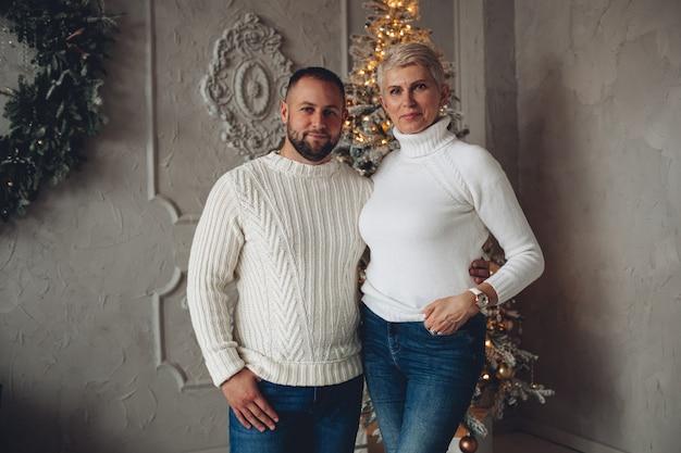 Erwachsene frau und junger mann tragen weiße pullover und stehen mit weihnachtsbaum auf dem hintergrund