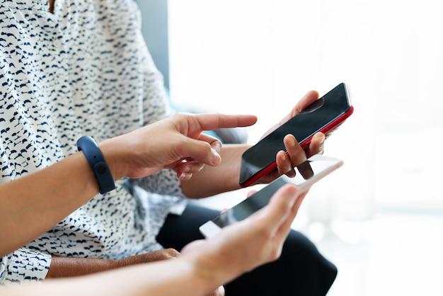 Erwachsene frau und tochter, die smartphone mit leerem bildschirm verwendet