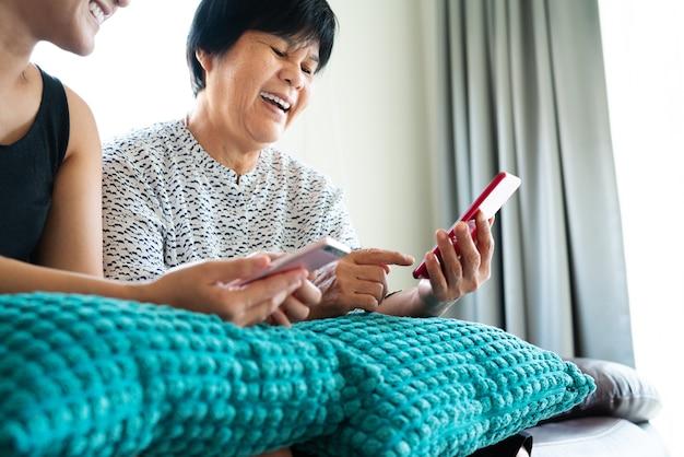 Erwachsene frau und tochter, die smartphone verwendet. lächelnder blick der frau handy