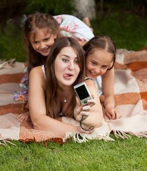 Erwachsene frau und zwei mädchen machen gesichter und machen fotos im park