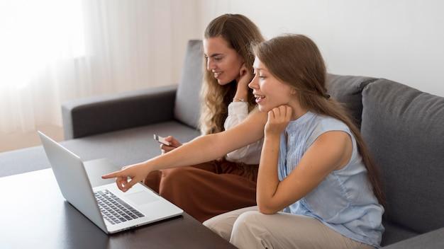Erwachsene frauen, die zusammen zu hause online einkaufen