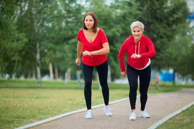 Erwachsene frauen in sportbekleidung bereiten sich auf einen sommerlauf im park vor