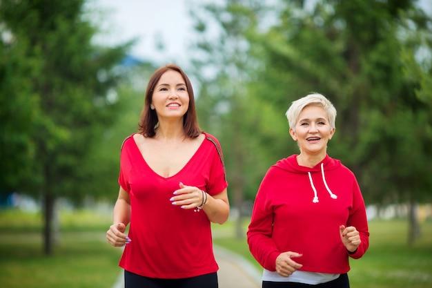 Erwachsene frauen in sportbekleidung laufen im sommerpark