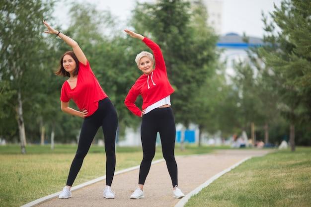 Erwachsene frauen in sportbekleidung machen im sommer übungen im park