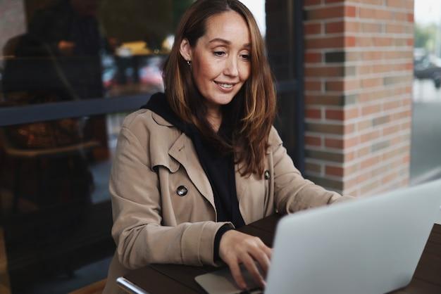 Erwachsene freiberufliche frau, die am laptop arbeitet