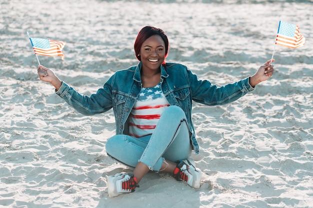 Erwachsene freundliche afroamerikanerfrau, die usa-flaggen hält