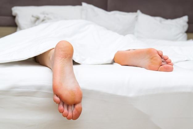 Erwachsene füße im bett mit weißer bettwäsche reinigen