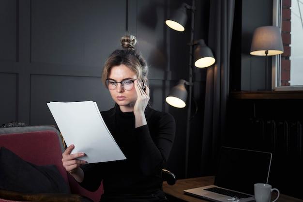 Erwachsene geschäftsfrau, die in papiere schaut