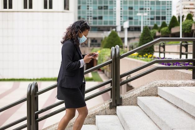 Erwachsene hispanische dame in bürokleidung und gesichtsmaske, die im finanzviertel der stadt spaziert.