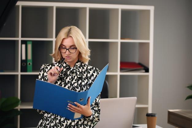 Erwachsene junge geschäftsfrau, die an ihrem büro arbeitet.