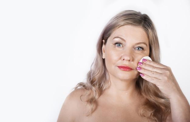 Erwachsene kaukasische blonde frau, die ihr gesicht mit einer baumwollscheibe säubert, die mit nackten schultern auf einer weißen wand aufwirft