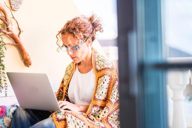 Erwachsene kaukasische frau mit warmer decke, die draußen zu hause mit einem laptop mit moderner technologie arbeitet und die terrasse und die freiheit vom büro genießt