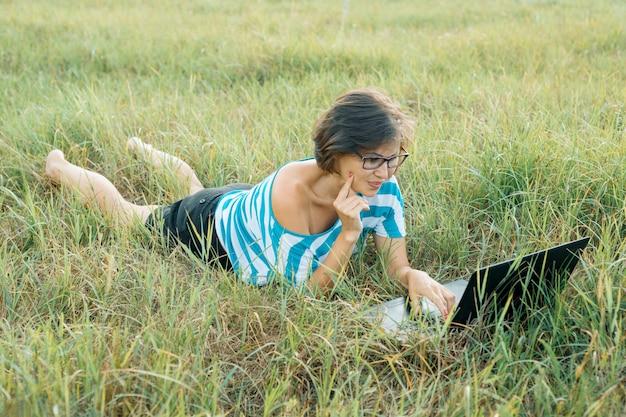 Erwachsene lächelnde frau, die computerlaptop auf gras verwendet