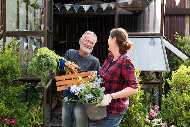 Erwachsene landwirte, die zusammen frisches lokales gemüse zeigend sprechen