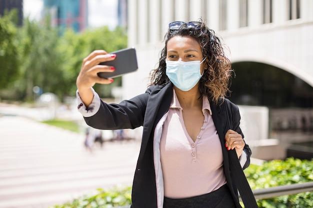 Erwachsene latina-frau, die ein foto mit handy macht. sie kleidet sich im freien formell mit gesichtsmaske.
