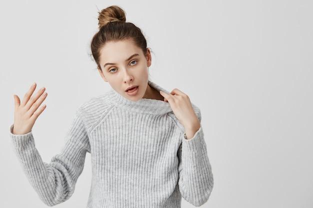 Erwachsene mädchen 20s mit hitzschlag gestikulieren sie braucht frische luft. frau mit dem haar im brötchen, das warme kleidung trägt, die heißes öffnen des mundes für atem fühlt. körpersprache