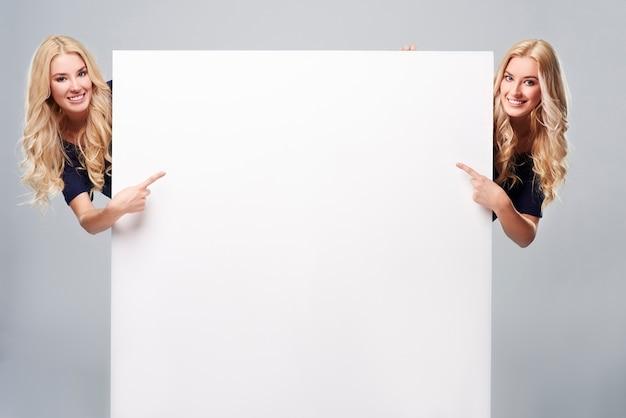 Erwachsene mädchen, die auf leeres plakat zeigen