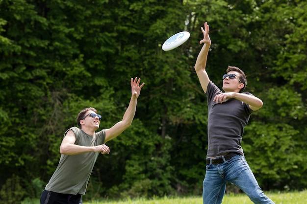 Erwachsene männer, die hoch springen, um frisbee zu fangen