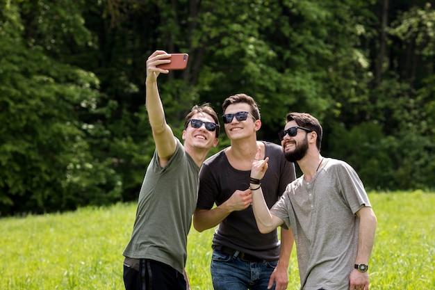Erwachsene männer, die selfie am telefon in der natur nehmen