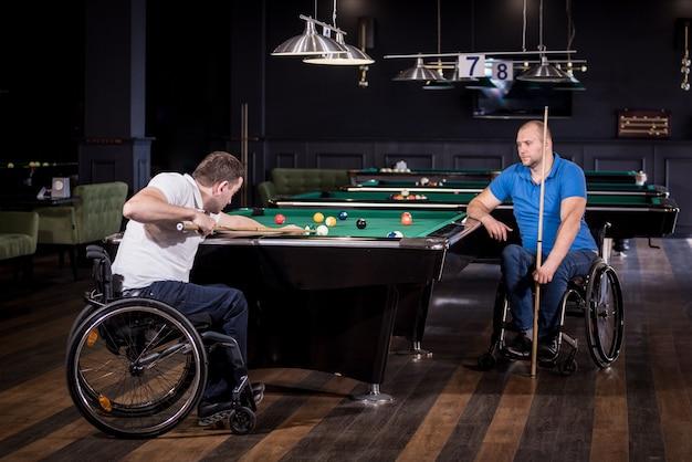 Erwachsene männer mit behinderungen im rollstuhl spielen billard im club