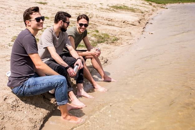 Erwachsene männer sitzen am strand mit beinen im wasser