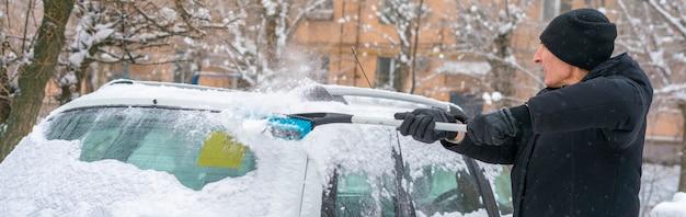 Erwachsene männliche saubere autowindschutzscheibe vom schnee im schneesturm
