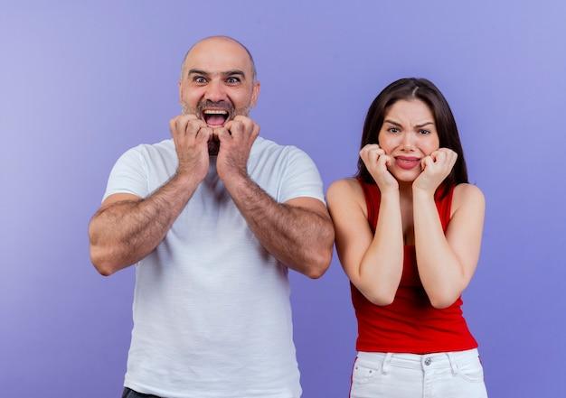 Erwachsene paare, die beide beeindruckt mann mit offenem mund kinn berühren und stirnrunzelnde frau gesicht berühren