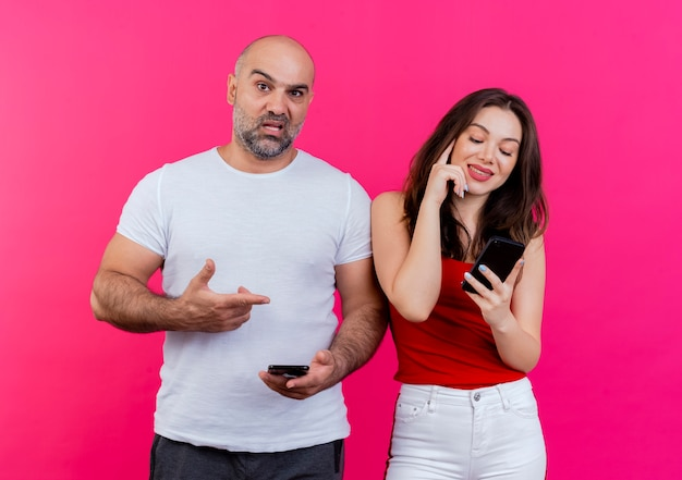 Erwachsene paare, die beide handys halten, beeindruckten den mann, der auf die frau zeigt, und die erfreute frau, die den kopf berührt, der den mann des telefons beeindruckt