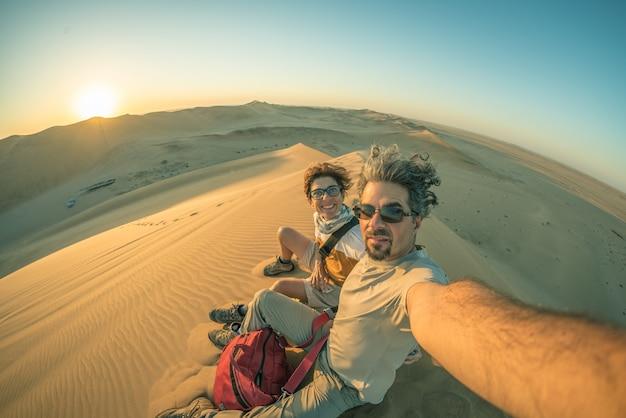Erwachsene paare, die selfie auf sanddünen nehmen