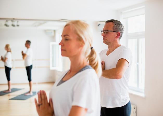 Erwachsene paare, die zusammen yoga ausüben