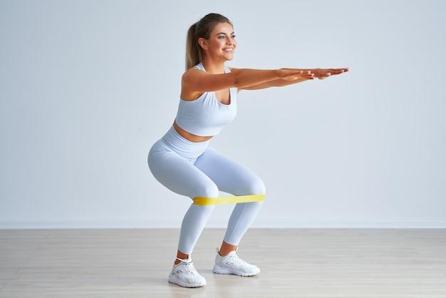 Erwachsene schöne frau, die mit pilates-gummibändern auf hellem hintergrund trainiert