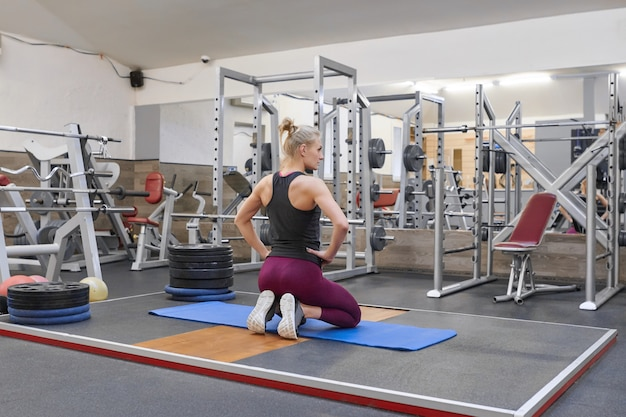 Erwachsene schöne weibliche blondine, die übendes yoga ausdehnend tut