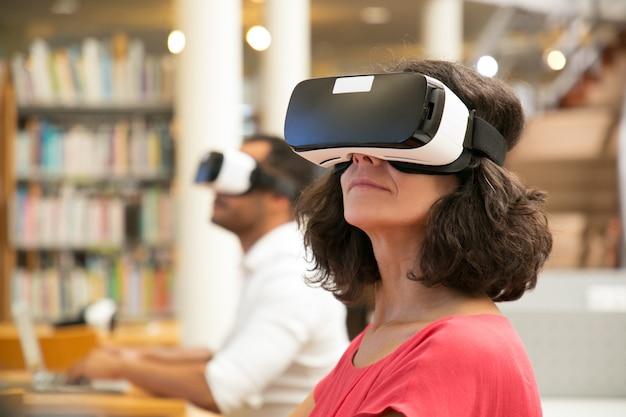 Erwachsene studentin, die virtuelles videotutorium in der bibliothek aufpasst