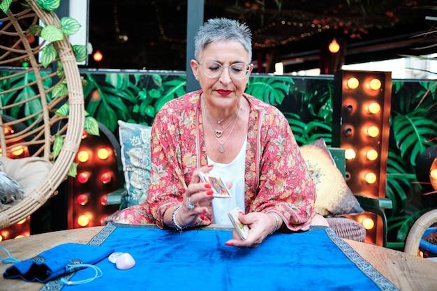 Erwachsene tarotfrau mit grauen haaren mit karten in der hand