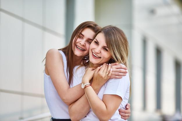 Erwachsene tochter umarmt mutter und beide lächeln in die kamera.