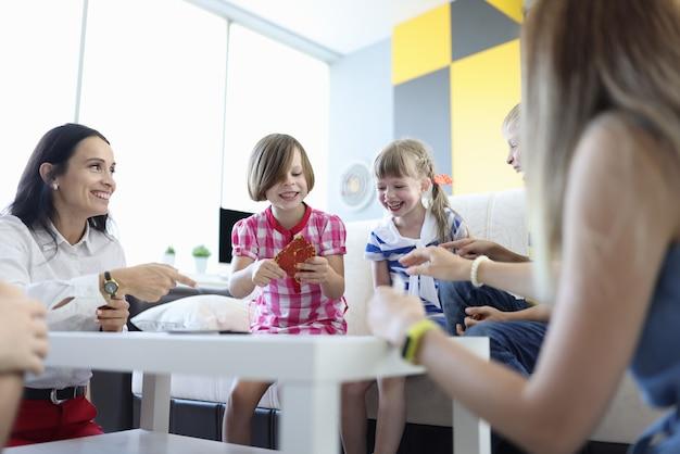 Erwachsene und kinder sitzen am tisch, halten spielkarten und lachen fröhlich