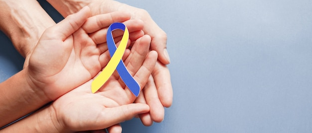Erwachsene und kinderhände, die blaues und gelbes bandförmiges papier halten, down-syndrom-bewusstsein, welt-down-syndrom-tag