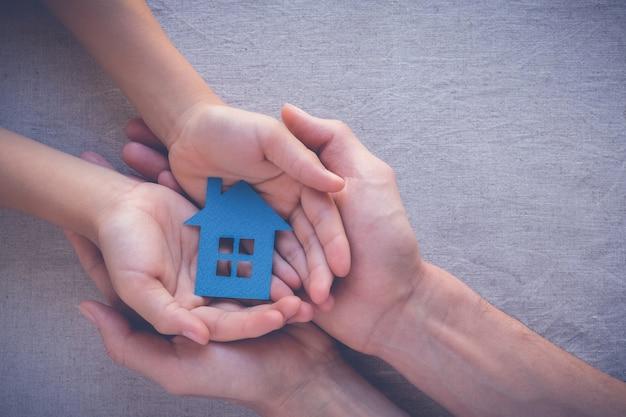 Erwachsene und kinderhände, die papierhaus, familienhaus und immobilienkonzept halten
