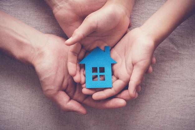 Erwachsene und kinderhände, die papierhaus, familienhaus und obdachloses schutzkonzept halten