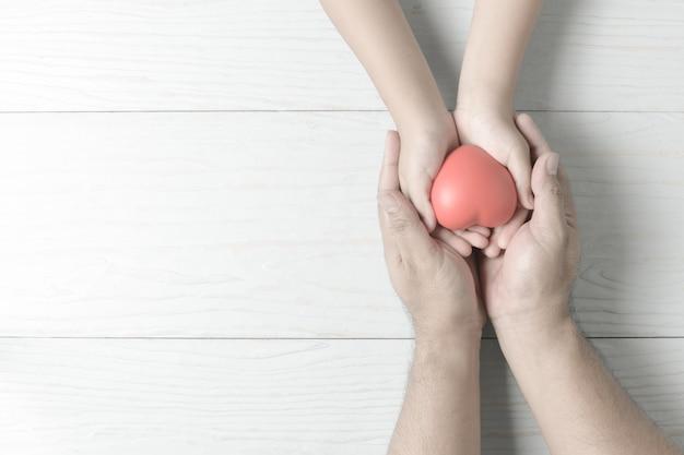 Erwachsene und kinderhände, die rotes herz auf weinleseton halten