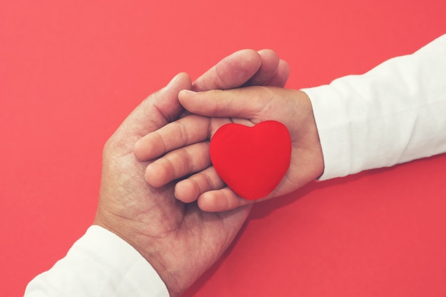 Erwachsene und kinderhände, die rotes herz halten, gesundheits-, spenden- und familienversicherungskonzept, weltherztag, weltgesundheitstag, csr-konzept, familienadoption fördern